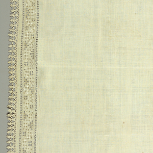 Oblong table cover with a border design in simple, geometric pattern. Trimmed with narrow pointed lace.