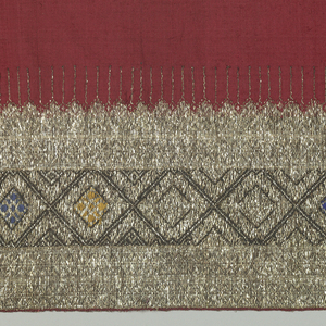 Fragment of a narrow border pattern. Red silk with design of lozenge shapes in flat silver foil strips.
