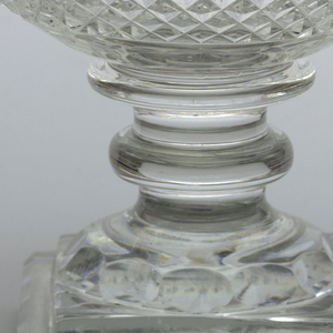 Round bowl with large turned-over rim on stem with 2 knops; high stepped square base with faceting cut around circular section top; sides of bowl cut with band of small diamonds, row of facets above and below, turned- over rim has small diamonds band and row of narrow fluting, star cut on bottom.