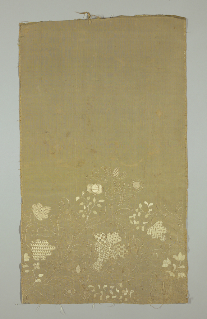 Embroidery, arranged as a border, in a design of flowers and leaves.