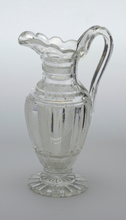 Tall ovoid body on flat circular stepped base, tapered neck, scalloped lip with pouring spout, loop handle notched for thumb; bottom of vase has deep cut radiating flutes, alternate ones with small diamonds, sides cut with alternate vertical pillar and diamond flutes, neck with same, horizontal.