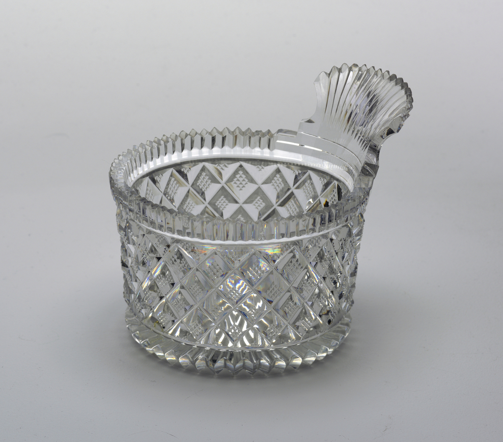 Straight sides cut with strawberry diamonds, top and bottom edges with vertical flutes, on the bottom the flute carried over to rayed fluting, fan shaped handle projecting from top edge, canted back, with vertical flutes.