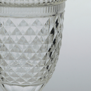 Slender urn-shaped body, cut with shallow diamond pattern all over, a row of thin fluting top edge, wider fluting at base; fluted stem on square base cut with star on bottom; tall bell-shaped cover cut with shallow diamonds and prismatic rings, faceted finial.