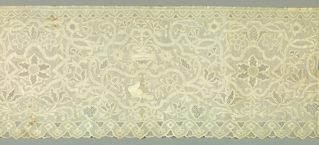 Oblong panel of very fine linen with elaborate design in fine drawn work in which the main lines of the design are reserved in linen. The background, centers of flowers and other small details are rendered in a variety of drawn thread patterns. In center, an urn with flower sprays and vines symmetrically arranged. Below is a bird, and at right and left, a symmetrical arrangement of curving vines and flowers of natural size. Lower edge is scalloped. Birds and other details are embroidered in white.
