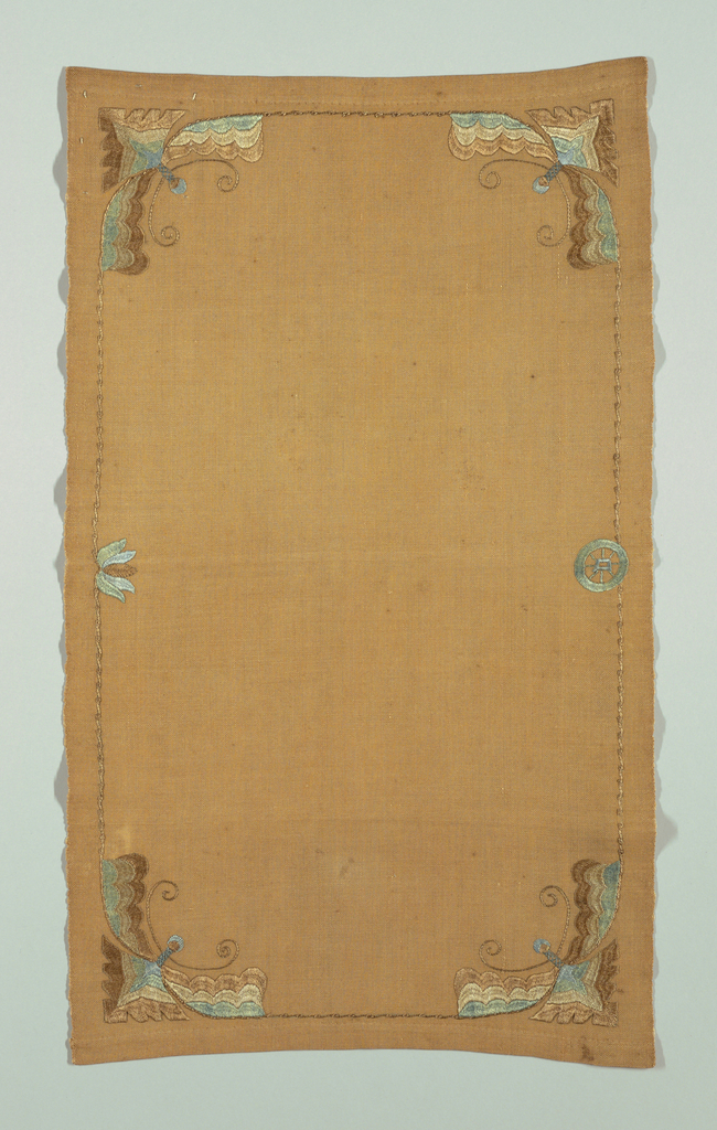"Light reddish-brown linen table mat with a stylized moth embroidered in brown, blue and green in each corner, facing the center of the cloth.  A signature ""D"" is embroidered within a wheel at bottom center."