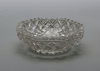 Small, octagonal dish with low, flaring sides. All-over crossent diamond pattern. Scalloped rim. Glass is heavy and white.