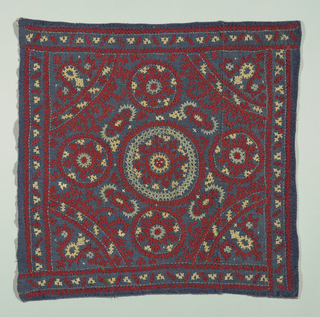 Embroidered square showing design of concentric circles and arcs embroidered with sharp sawtooth edges in red, blue and ivory silk.