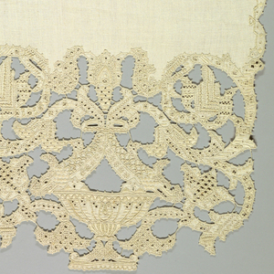 Long rectangular cover with deep cutwork and embroidered border at both ends in a pattern of a vertically symmetrical urn and flowering vine.