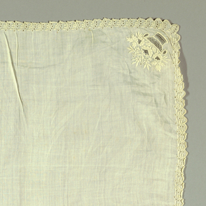 "Square of fine linen with narrow scalloped border of tiny pierced sprig repeat in white cotton. Small flower basket with lace filling stitches in opposite corners. In alternate corners, footed vase containing large rose, leaf, and fine flower detail. ""Pauline"" above one; ""Rousseau"" above the other."