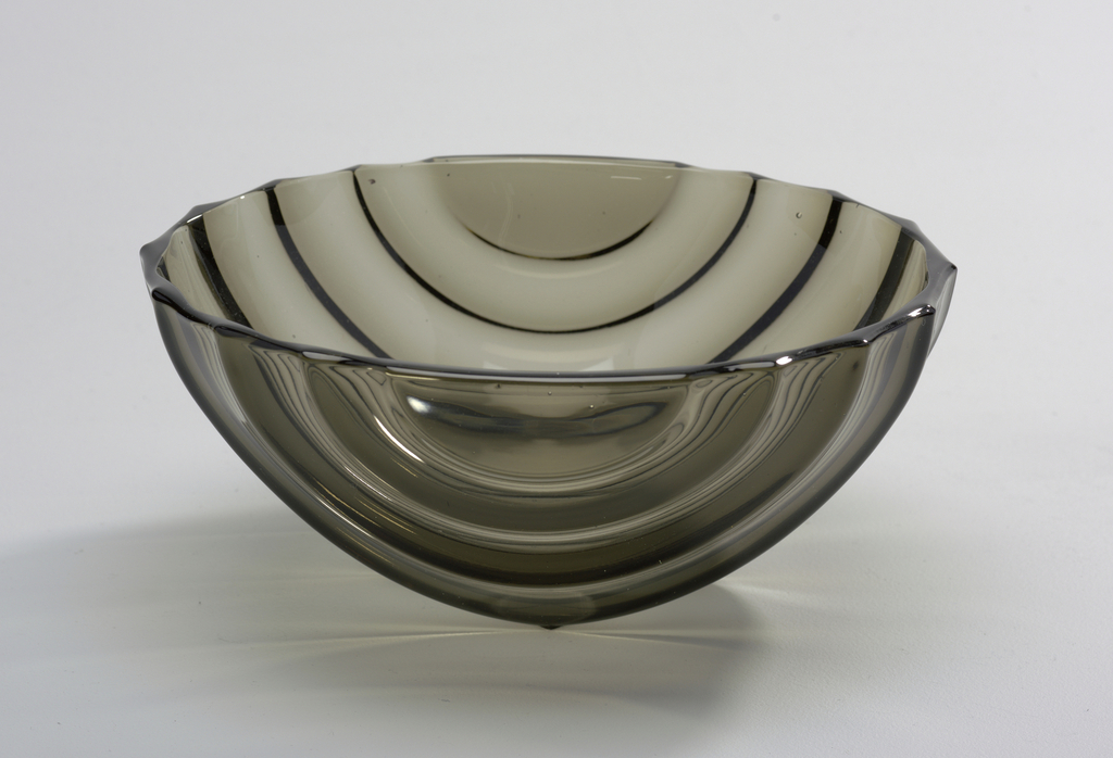 A footless glass bowl with a purple tint. The bowl has varying thickness in a striped pattern on the outside.