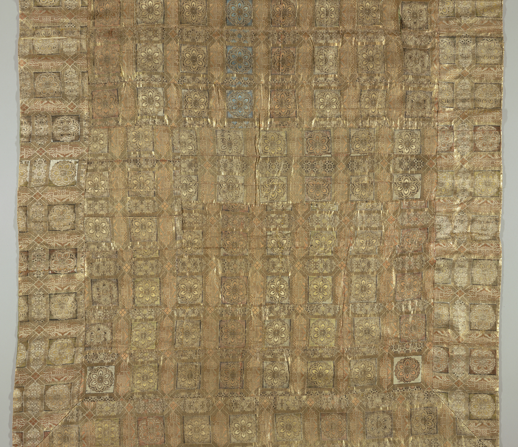 Large rectangular panel made of many small rectangular pieces of gold cloth. Gold rosettes in squares alternate with elongated hexagons filled with diapers or landscapes. Silks in soft blue, peach and yellow bound in twill weave adn gilded paper strips bound in plain weave fill subordinate areas of these designs. Pulp paper backing; green silk facing.