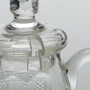 Barrel shaped body with flat, cushion cover and round, faceted finial; loop handle. Flat base, star cut on underside. Alternating vertical panels of small diamonds and herringbone below double band of printies. Cover has printies and spoon notch.