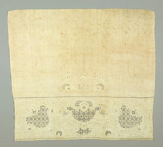 "Towel end with deep border at bottom of three flower heads in drawn work with fine embroidered foliage detail, in white linen thread. Initials ""I.A.D."" in symmetrical leaf-framed cartouche above. Two plain selvages. Hand-stitched hems at top and bottom."