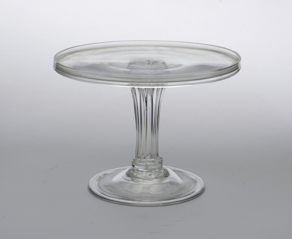 Circular tray with up-turned rim; molded and shouldered stem; circular domed base with turned-under edge.