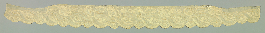 One sleeve edging or short ruffle embroidered in design of flowers and leaves arranged around curving band.