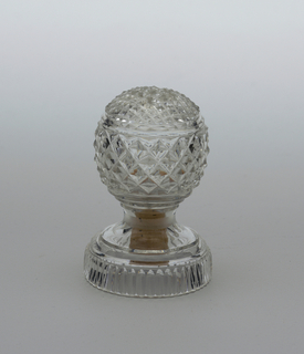 Globular body, on stemmed circular foot. body decorated with diamond cutting, and prismatic rings. Diamonds on upper portion are smaller and contain holes for pouring. Hole for cork on bottom of foot.