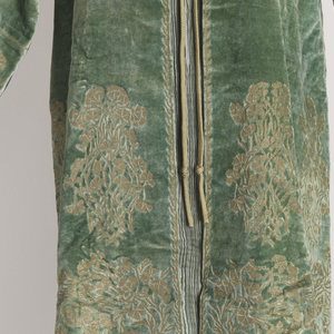 Sleeveless Delphos dress in seafoam green pleated silk, with drawstrings to gather at the shoulder and Murano glass beads down the side seams. Matching silk velvet three-quarter length coat stenciled in gold with a Persian design of a cluster of carnations.