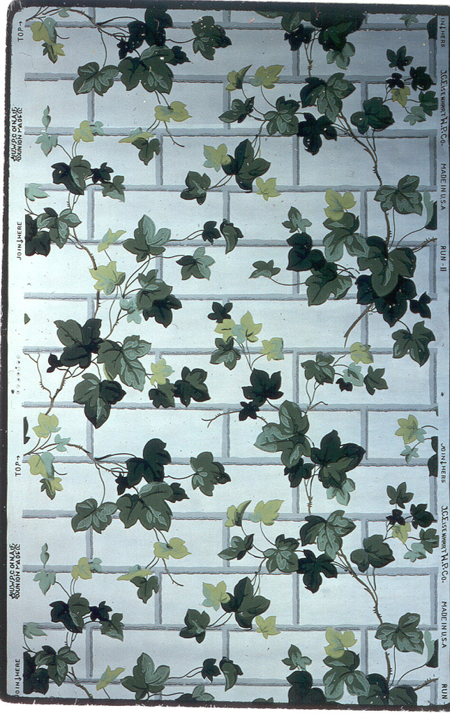 Ivy leaves in all shades of green winding on a grey brick facade on a white ground.