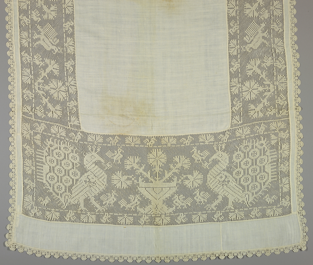 Cover of white linen with wide borders of embroidered net with a design of a flowerpot with carnations and confronted peacocks on either side. Edged with scalloped bobbin lace.