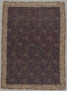 Rectangular panel of fine twill tapestry has a tight arrangement of small-scale quatrefoils and ogives enclosing flowers with interspaces filled with floral and foliate motifs. Colors are dark red, blue, green, purple, yellow, and white. Bordered and piped with different bands of imitation tapestry, one floral, one geometric. Backed with red cotton twill.