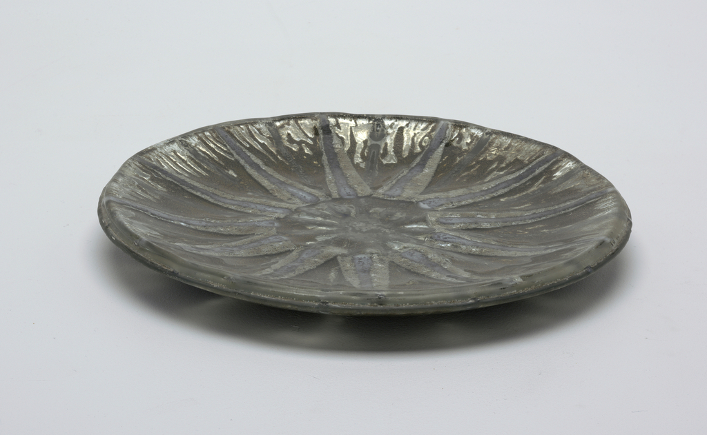"Circular plate consisting of three layers of sheet glass ""slumped"" in mold.  Star-shaped ornament in silvery tones on gay, achieved by metal foil and streaks of glaze arranged between the layer of glass.  Scratched in signature on back: ""Earl McCutchen""."