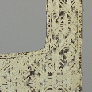 Border for a tablecloth in net darned with a pattern of angular scrolling vine with foliage and blossoms pointing alternately up and down. Two ends have double design placed back to back.