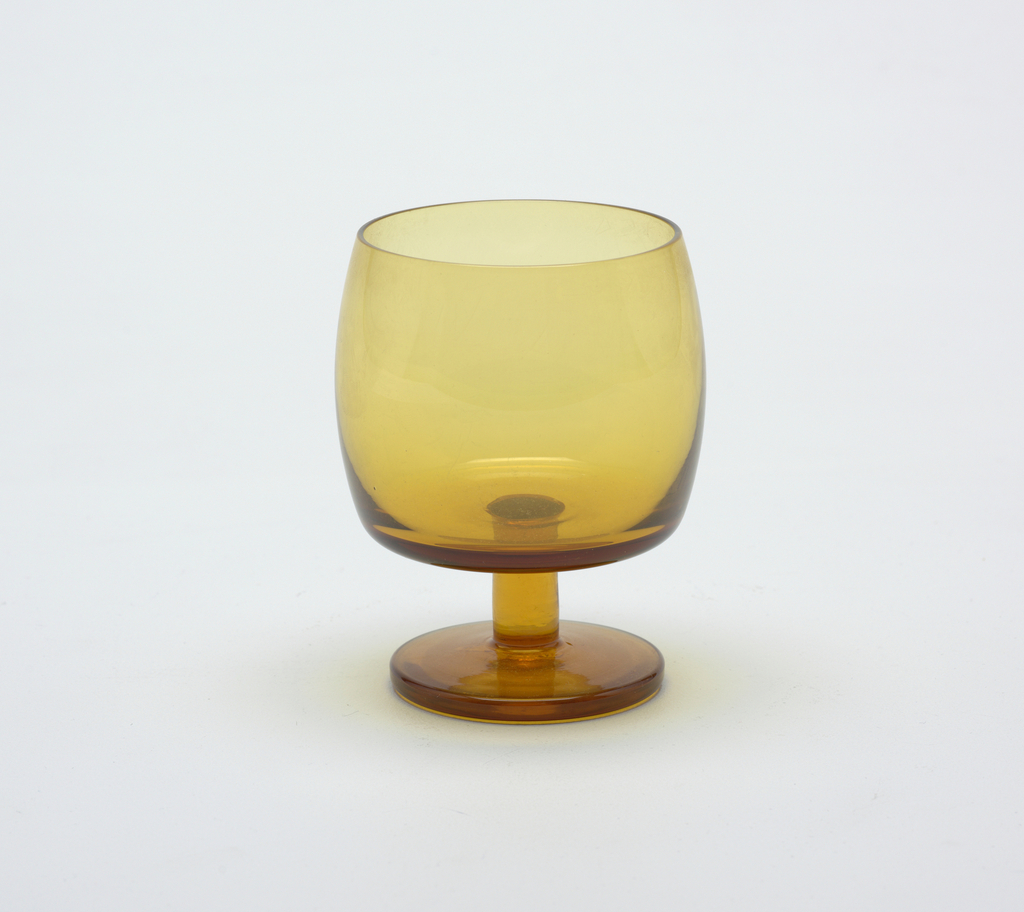 Smokey-yellow transparent cylindrical body, slightly convex, on a short cylindrical stem with circular foot.