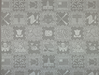 White openwork casement fabric with a straight repeat containing the Liberty Bell, early American flag, crossed rifles, eagle, scroll and pen, cannon, fife and drum, 1776-1976, Ben Franklin's kite, George Washington crossing the Delaware River, and Independence Hall – each enclosed in a scroll frame.