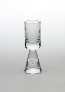 Clear transparent cylindrical cup on solid conical base.
