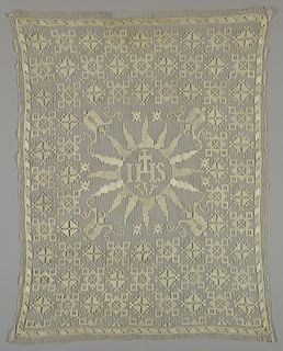 "Altar frontal with central design of a sunburst containing the letters ""IHS"" with a cross extending upward. Stylized geometric pattern surrounds with central motif."