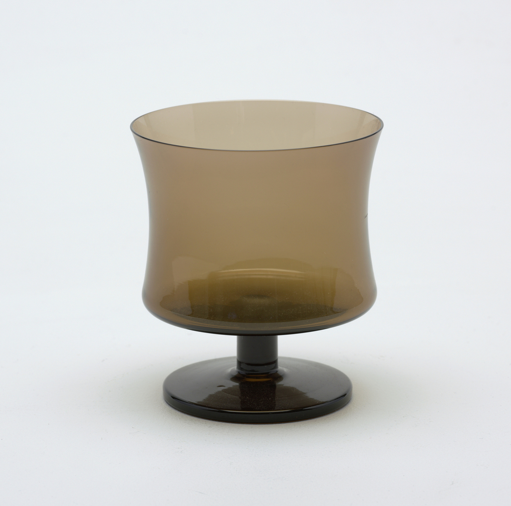 Smokey-brown transparent cylindrical body, slightly concave, on a short cylindrical stem with circular foot.