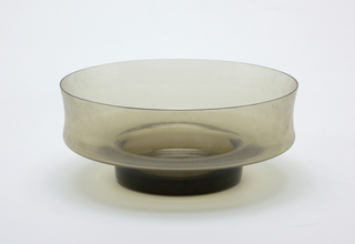 Transparent smokey brown circular bowl with concave wall and short circular base.