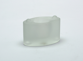 Oval stackable glass candle holder with a frosted finish, part of a set. Concave circular opening on the top for candle.