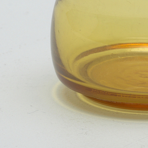 Smokey-yellow transparent cylindrical body of two convex sections, one above the other.