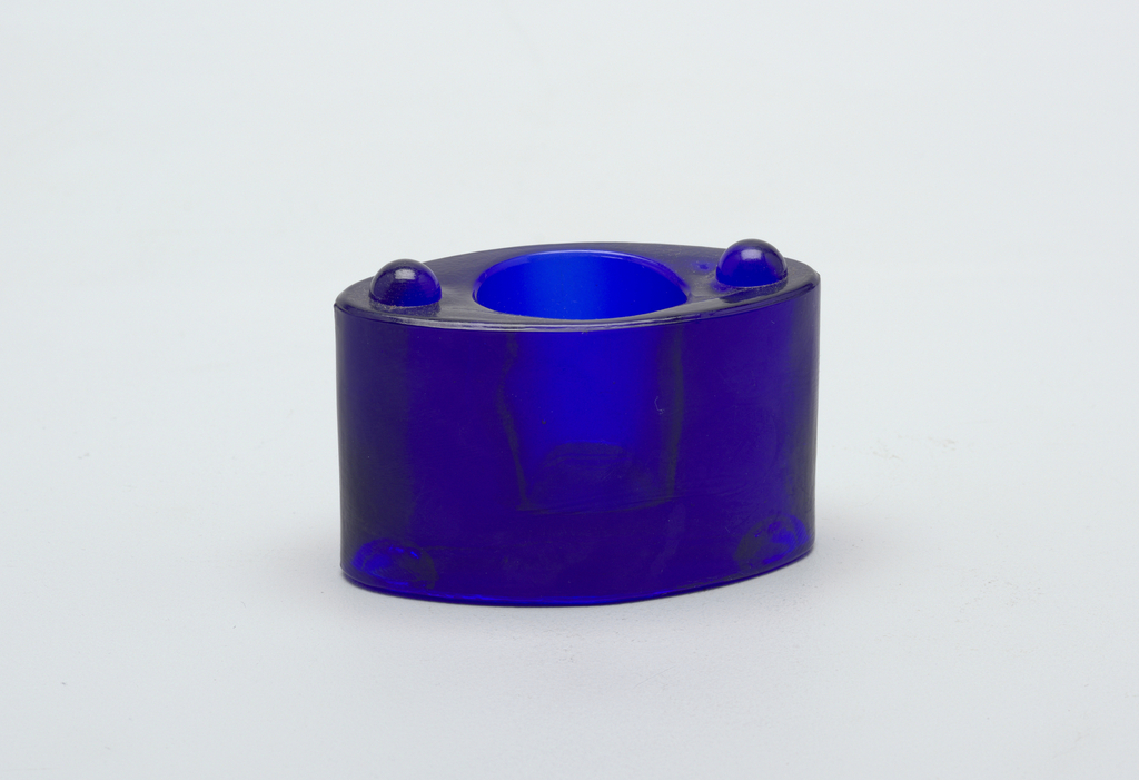 Oval, stackable blue glass candle holder, part of a set. Concave circular opening on the top for candle; two buttons at either side of top and two corresponding cavities on underside to secure for stacking.
