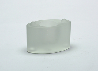 Oval, stackable glass candle holder with a matt finish, part of a set. Concave circular opening on the top for candle; two buttons at either side of top and two corresponding cavities on underside to secure for stacking.