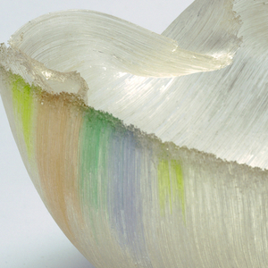 Hemispherical bowl formed of layered clear glass threads.  Individual threads pulled and slumped into form, edges manipulated to create irregular folds and indentations.  At one edge, transparent yellow, blue, green and pink threads intermixed to create pastel color passage; opposite edge with yellow threads only.