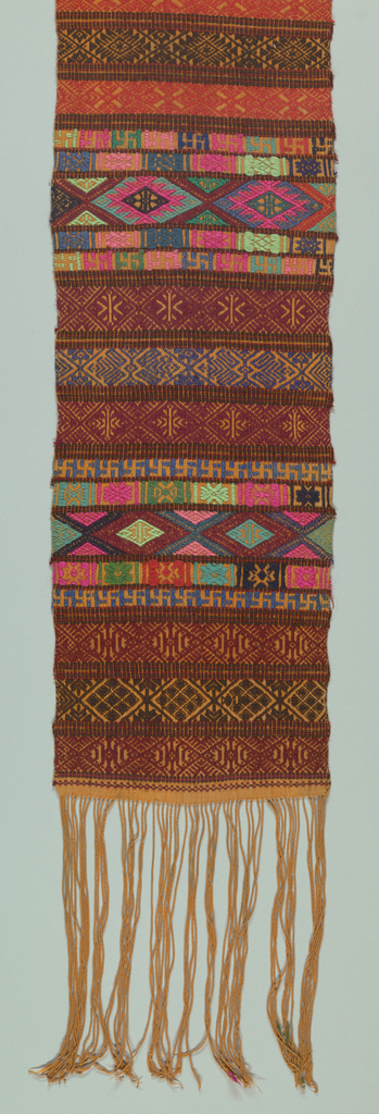 Man's sash of orange cotton, embroidered in small scaled geometric pattern in reds, greens, pinks, blues, black and turqoise. All over pattern running in horizontal stripes.