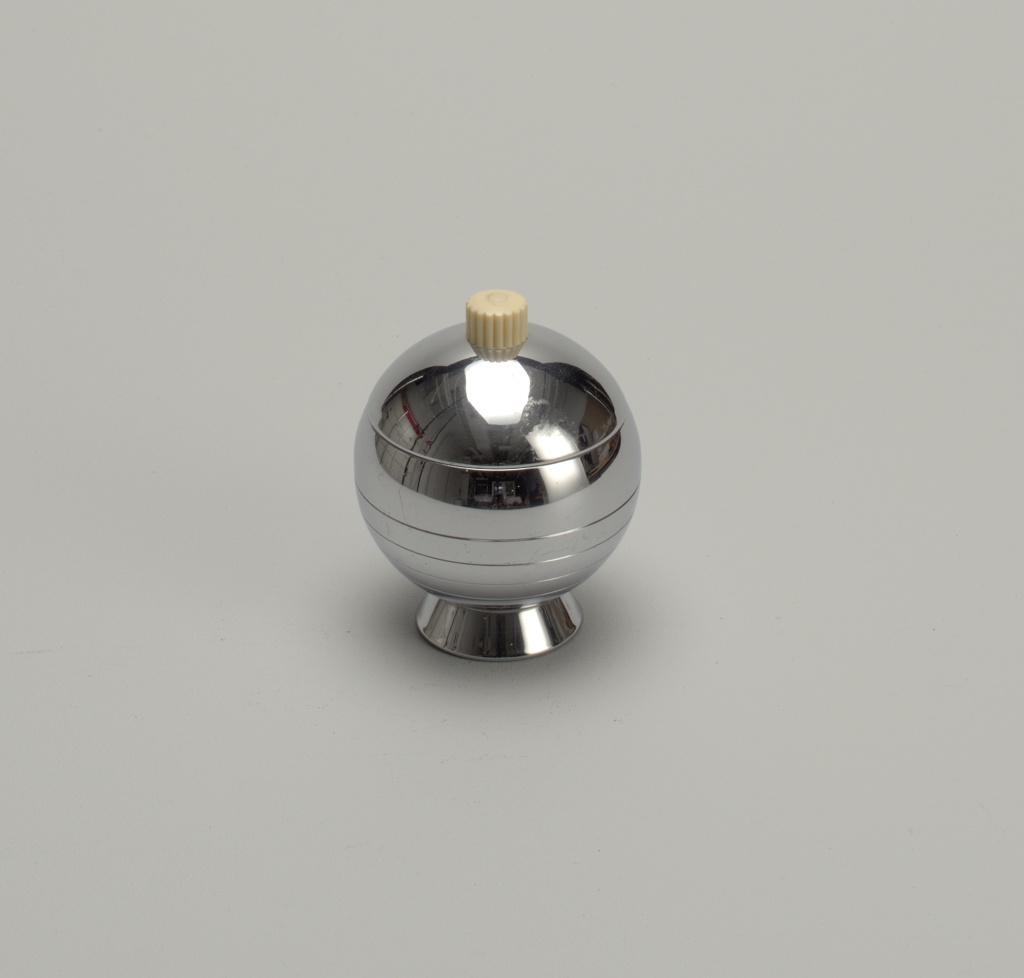 Sphere shaped chrome sugar bowl with a chrome lid with a cream plastic knob. Sugar bowl sits on a small chrome cylindrical base.