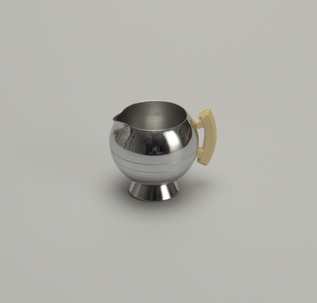 Sphere shaped chrome creamer with an open top and small spout. Sugar bowl sits on a small chrome cylindrical base.
