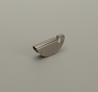 Bottle opener formed of circle of metal, bent to form two semicircular upright sides and broad central channel. Channel pierced at one end with oval hole to create lip for opening bottle.