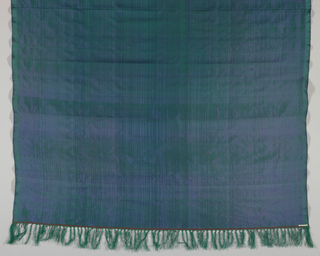 Shawl with a green warp and blue weft in changeable green and blue vertical stripes. Green fringe at either end.