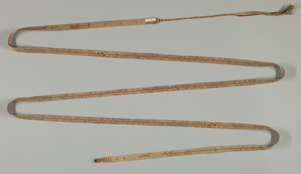 Long red and ivory tape with inscription in the Pali language of Burma. It was used to tie palm leaf manuscripts. Tape ends with a long braid of the warp