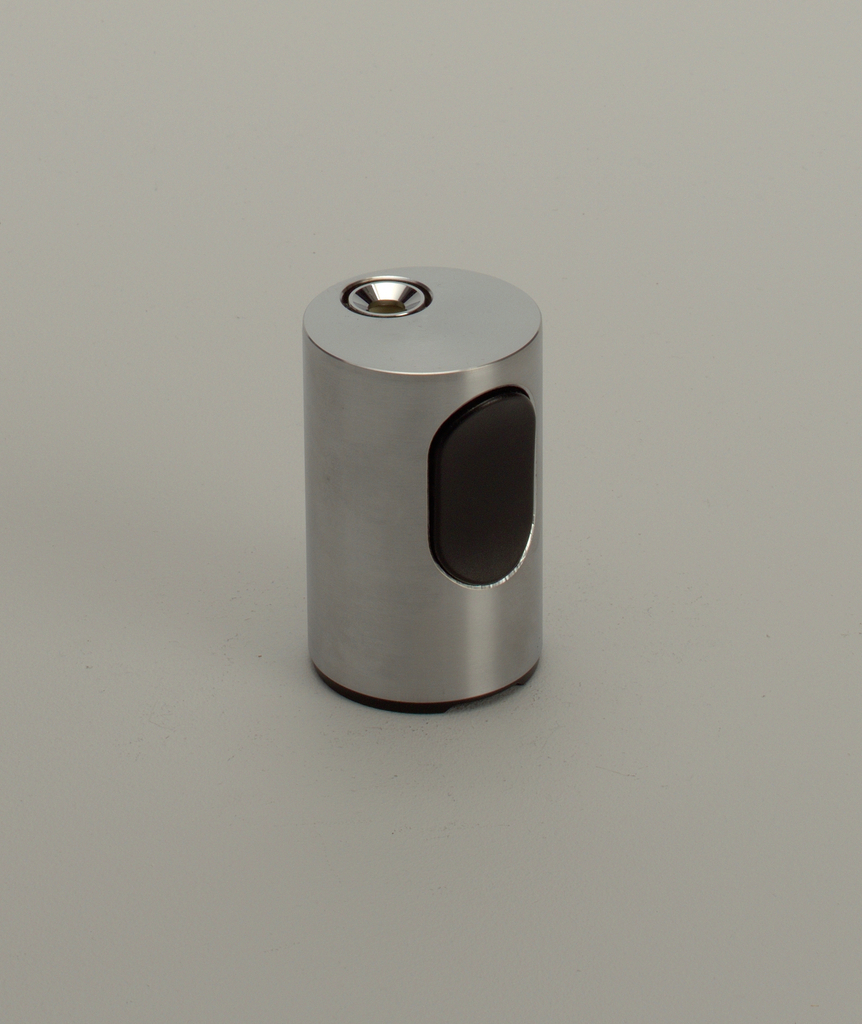 Table lighter of cylindrical form with matt surface; top with indented circular flame outlet set off-center; large black oval ingition button on side; circular black base plate.