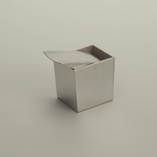 Slightly flaring rectangular box with slab-like, pivoting flip-top lid, its thin edge projecting beyond one side of box; all of polished aluminum.