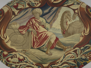 """Oval fragment representing """"Asia"""" shows a seated man in a turban and loose robe. Behind him is blue fringed tent panel and two camels. He carries a scepter and a sword rests near his feet. In shades of red, blue, brown and off-white. Probably a detail from a table cover."""