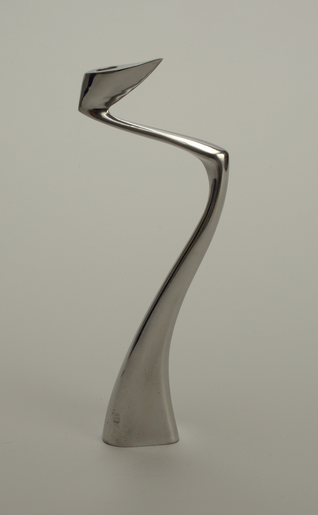 Curvilienar zig-zag form with thick, canted nozzle at top tapering to narrow diagonal neck above curving vertical shaft that broadens to triangular base.