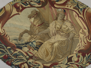 """Oval fragment representing """"Europe"""" shows a seated female figure, crowned and holding a scepter. Behind her is a panel of red drapery and a rearing horse. Grapes and other fruits are by her feet. In shades of red, blue, brown and off-white.  Probably a detail from a table cover."""