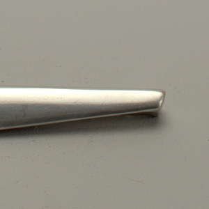 Cast, polished aluminum. Overall triangular shape, with tapered extension at lower edge to form grip; upper edge chamfered, with recessed central section; reverse with flat section for attachment with two drilled holes for screws.