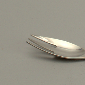 Integral. Oval bowl, pierced to create three tines.